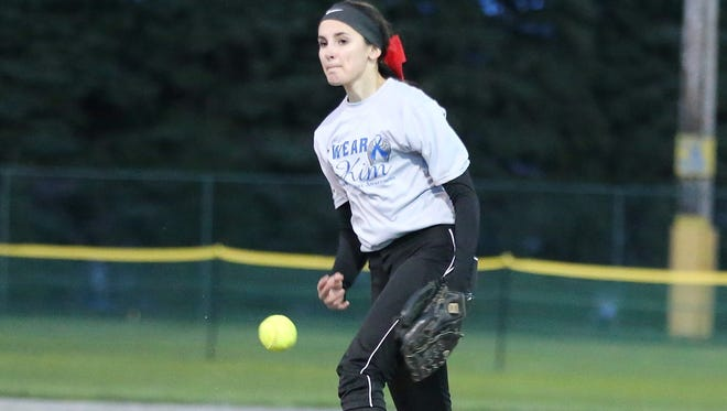 Livonia Churchill junior pitcher Paige Hanson flings the ball during Monday's benefit game for colon cancer research. She is wearing   a T-shirt honoring her mom, Kim Hanson, who died in January from the disease.