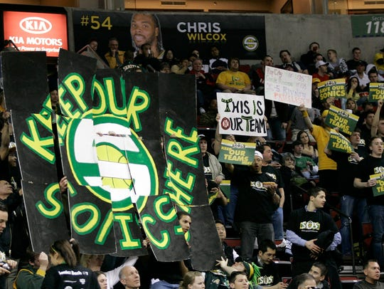 Seattle SuperSonics fans hold signs in favor of keeping