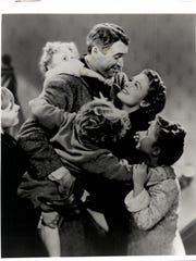 "Actor James Stewart, with Donna Reed and other cast members in a photo from the 1946 classic movie ""It's a Wonderful Life,"" remains an influence in the town he hasn't lived in for decades."