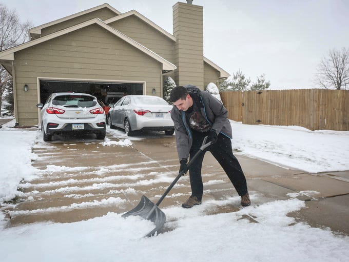 Justin Snyder clears his driveway in West Des Moines
