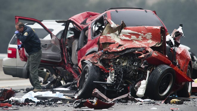 Officials investigate the scene of a multiple vehicle accident where six people were killed on the westbound Pomona Freeway in Diamond Bar, Calif., on Feb. 9, 2014. Authorities say a wrong-way driver caused the predawn crash that left six people dead.