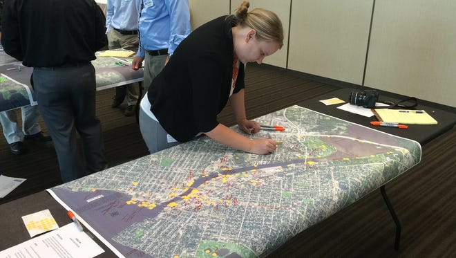 Oshkosh Assistant Planner Elizabeth Schultz reviews comments and stickers left on one of several riverfront visioning maps used Wednesday evening.