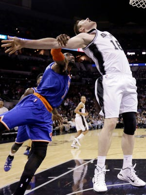 The San Antonio Spurs' Aron Baynes is fouled from behind by the Knicks' Amar'e Stoudemire during the second half of Wednesday night's game.