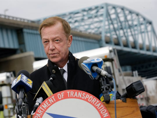 New Jersey State Transportation Commissioner Jamie Fox answers a question about the closure of the right lane of the Route 3 bridge eastbound, seen behind, over the Hackensack River, that leads to the Lincoln Tunnel Thursday, Jan. 22, 2015, at the Department of Transportation maintenance yards in Secaucus, N.J. The right-hand lane on the bridge eastbound was closed Wednesday because of cracks in its support structure. The lane will remain closed until repairs are complete in about two weeks. (AP Photo/Mel Evans)