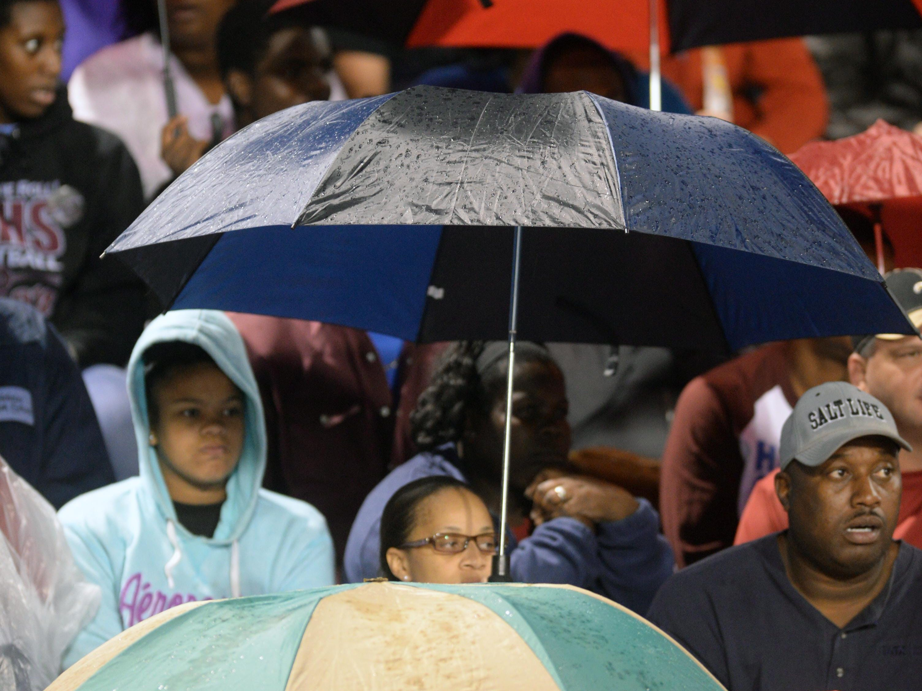 Fans take cover as the rain begins to fall during the North DeSoto takes on Minden game Friday night.