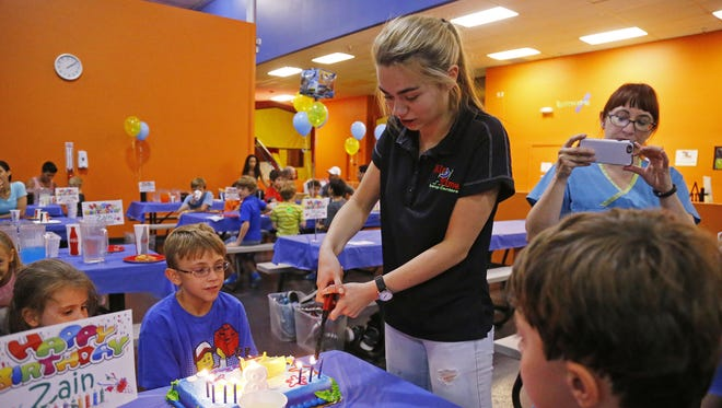 Birthday party coordinator, Alex Cetwinski, lights birthday candles for Zain Curtis, 8, at  AZ Air Time Indoor Trampoline Park & Family Fun Center in Scottsdale.
