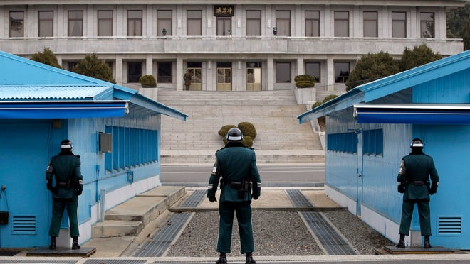 FILE - In this March 12, 2014, file photo, a North Korean soldier, top, looks at the South side as three South Korean soldiers, foreground, stand guard at the border village of Panmunjom, which has separated the two Koreas since the Korean War, in Paju, South Korea. South Korea is one of the safest places in the world to live and visit. But it's also an easy drive to the edge of an incredibly hostile, and nuclear-armed, North Korea. Since U.S. President Donald Trump has begun matching the over-the-top rhetoric North Korea has always favored, there have been worries over the possibility of war. (AP Photo/Lee Jin-man. File)