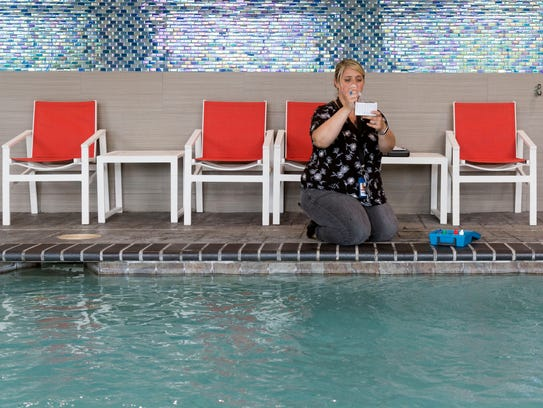 Camila Almeida of the Knox County Health Department inspects the water of the indoor pool at Holiday Inn Express on Papermill Drive on Monday, May 21, 2018.