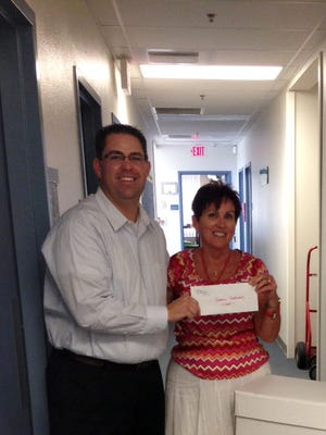 Bank of Nevada President Dan Wright, left, delivers school supplies and cash to VVES Principal Cathy Davis.