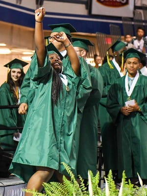 A graduate celebrates as she walks to receive her diploma on Saturday, May 27, 2017, during the Hoover High School graduation at the Drake University Knapp Center.