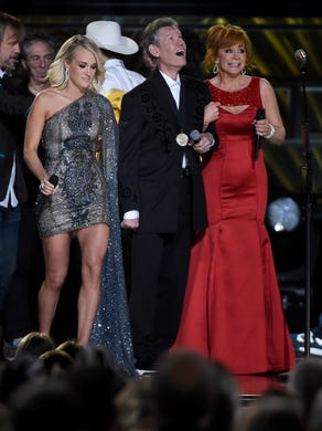 Co-host Carrie Underwood and Reba McEntire onstage