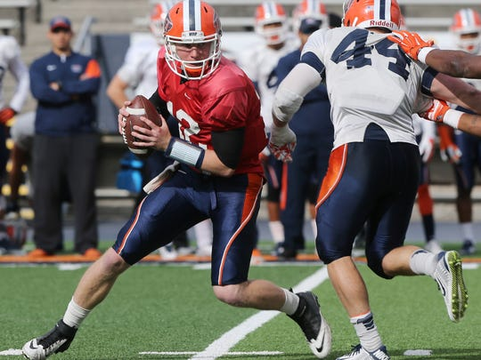 UTEP quarterback Ryan Metz evades charging defender Cooper Foster during Friday's scrimmage at the Sun Bowl.