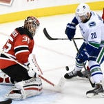 New Jersey Devils goaltender Cory Schneider (left) deflects a shot by the Vancouver Canucks' Chris Higgins during the third period of Friday's game in Newark. The Devils won 4-2.