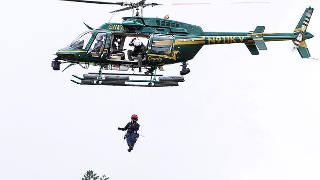 Marion County Sheriff's Office helicopter pilot Sgt. John Rawls hovers over a mock victim last Wednesday during a training exercise. Sheriff's Sgt. Darren Bruner runs the hoist while lowering Marion County Fire Rescue firefighter/paramedic David Cooper. The Helicopter Search And Rescue Team, or HSART, is a joint effort between the sheriff's office and Marion County Fire Rescue. The sheriff's office flies the helicopter and runs the hoist while fire rescue personnel respond to the victim. This exercise was carried out at the Ocala International Airport.