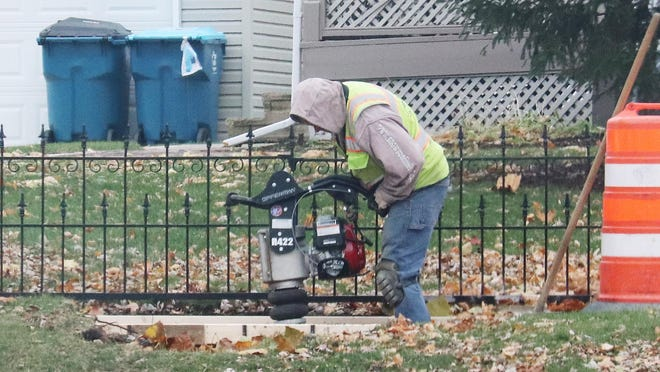 An Opperman Construction employee stamps the ground along a sidewalk on North Main Street. Utility work is taking place along North Main.