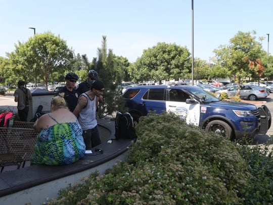 Redding police officer Nicholas Day, center, and Anderson police officer John Greene search a man Aug. 10 in front of Safeway on Pine Street.