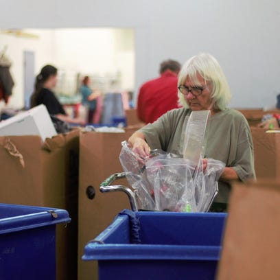 Connie Rehm sorts through donations in the warehouse