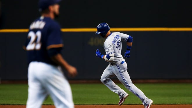 Toronto's Jose Bautista rounds the bases after hitting a home run off the Brewers' Matt Garza in the fourth inning Wednesday afternoon at Miller Park.