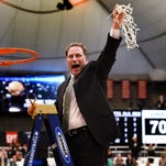 Michigan State coach Tom Izzo holds up the net after his team defeated Louisville in the East Regional final on Sunday in Syracuse, N.Y.