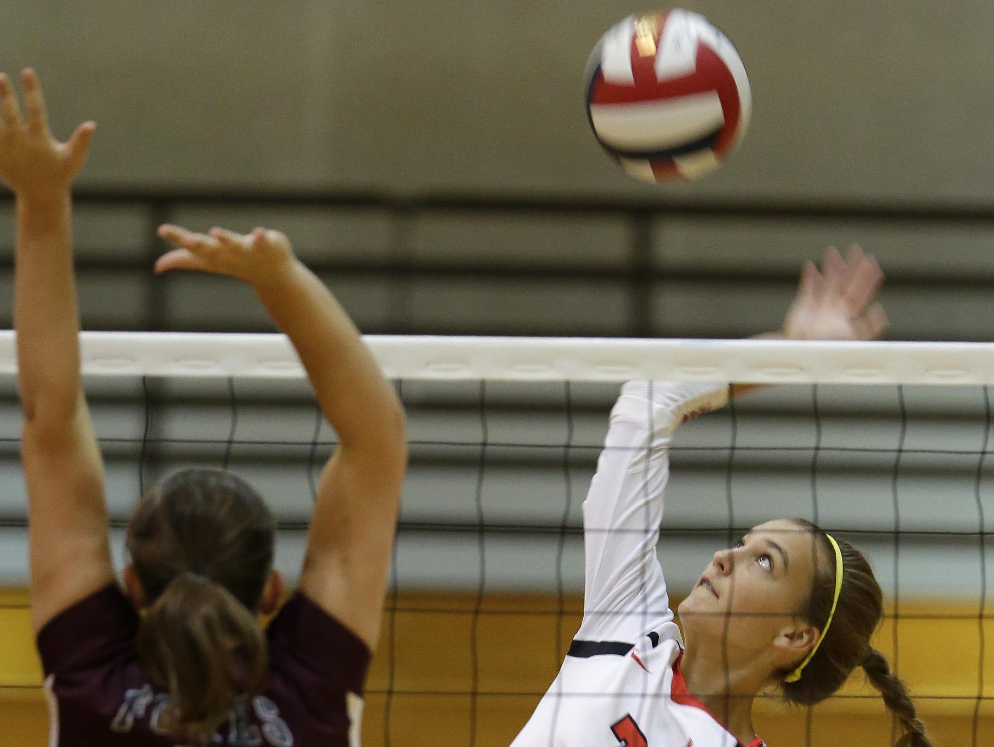 Neenah High School's No. 7, Addie Barnes, spikes against Fox Valley Lutheran High School's No. 9, Alexis Uitenbroek, during the 2015 Battle of the Valley volleyball invitational on Aug. 25 in Neenah.