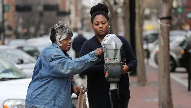 Brittany Toler (right) and Flora Amison, both from North College Hill, feed their parking meter in downtown Cincinnati.