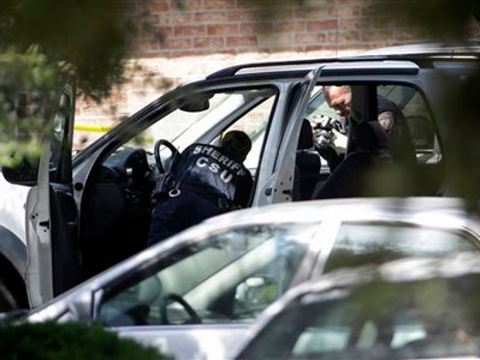 Members of the Harris County Sheriff's Department Crime Scene Unit process a vehicle outside the home where multiple people were found shot Sunday, Aug. 9, 2015, in Houston. Eight people, including five children and three adults, were found dead inside a Houston-area home following the arrest of David Conley, who exchanged gunfire with police, Texas authorities said Sunday.