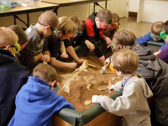 Mini-paleontologist dig for fossils at Dinosaur Discovery