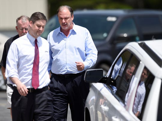 Michael Strickland, center, and Nate Evans, second from left, Stickland's attorney, arrive at Bandit Lites, the scene of a law enforcement raid in Knoxville on Thursday, May 14, 2015.