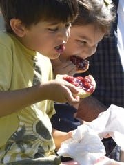 Mattias Velazquez of Arlington, Illinois, and his cousin Lucianna Barraza, dig into cherry-topped kolaches during Cherry Fest last year at Lakeside Park in Jacksonport. This year's festival is Aug. 4.