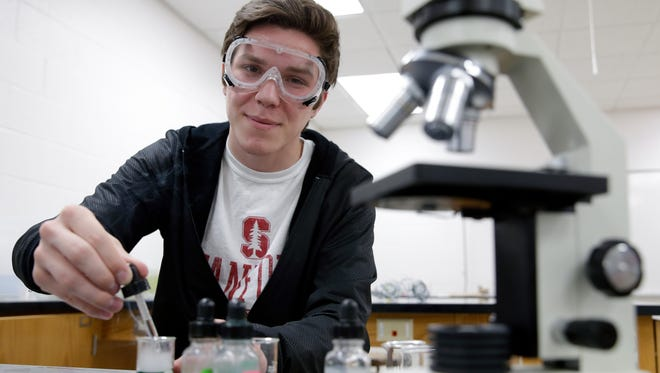 Ashwaubenon High School senior Tyler Johnson demonstrates chemical reactions in one of the school's science classrooms. Johnson is one of 10 students chosen for this year's Green Bay Press-Gazette Academic Team.