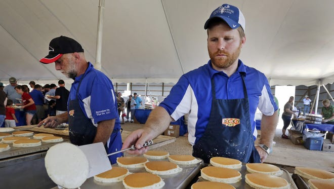 Joe Potter of Hartford, right, flips pancakes during Breakfast on The Farm at Majestic Crossing Dairy near Sheboygan Falls.