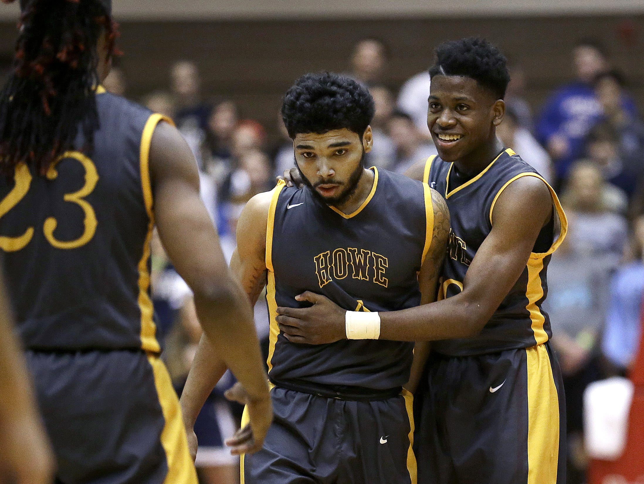 """Howe's Rashawn Rush, right, begins to celebrate with Brian """"Kip"""" Warren (center) as they defeated Providence in the IHSAA Class 2A semistate March 19, 2016."""