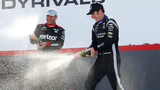 FILE -- Will Power, left, of Australia, who finished in second, and teammate and race winner Simon Pagenaud, of France, spray sparkling win as they celebrate in Victory Lane at the IndyCar Honda Indy 200 auto race Sunday, July 31, 2016, at Mid-Ohio Sports Car Course in Lexington, Ohio. (AP Photo/Tom E. Puskar)