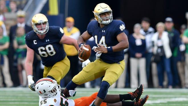 Notre Dame Fighting Irish quarterback DeShone Kizer (14) is sacked by Miami Hurricanes linebacker Shaquille Quarterman (55) in the second quarter at Notre Dame Stadium.