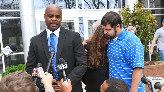 Kathy Mendez center, is comforted by her son Raven Flores outside the Greenville County Courthouse as Bruce Wilson left, of Fighting Injustice Together makes a statement to the media after watching police video of Mendez's son Jason Mendez being killed in an officer-involved shooting on February 11th.