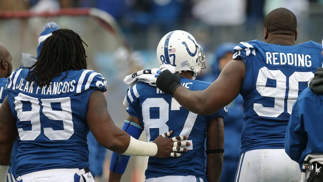 Colts defensive end Ricky Jean Francois and teammate Cory Redding give wide receiver Reggie Wayne a little extra support after Wayne's long pass reception in the second quarter Sunday.