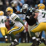 Green Bay Packers quarterback Aaron Rodgers (12) avoids being sacked by Carolina Panthers defensive end Kony Ealy (94) during Sunday's game at Bank of America Stadium in Charlotte, NC.