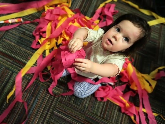After all the confetti and streamers have fallen, Madeline Cruz plays with the colorful leftovers during the New Year's at Noon: Superhero Spectacular at the Children's Museum Saturday.