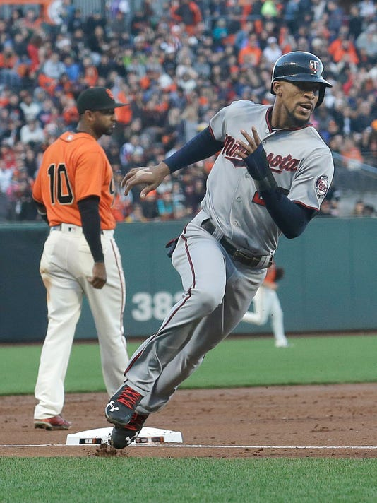 Minnesota Twins' Byron Buxton, right, rounds third base past San Francisco Giants third baseman Eduardo Nunez on the way to scoring during the third inning of a baseball game in San Francisco, Friday, June 9, 2017. (AP Photo/Jeff Chiu)
