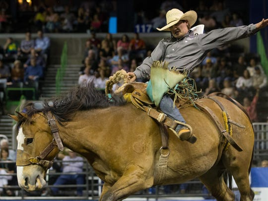 A saddle bronc rider competes on the first night of