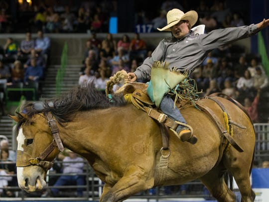 A saddle bronc rider competes on the first night of the Corpus Christi Rodeo at the American Bank Center on Thursday, April 27, 2017.