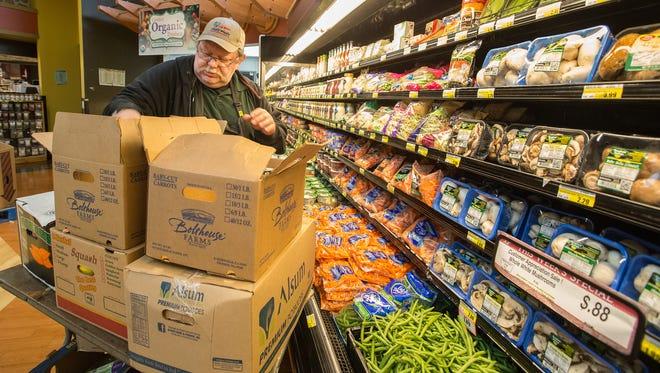 Dan Alpertin stocks the produce shelves at Fox Bros. Piggly Wiggly store in Oconomowoc.