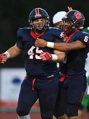 Belton-Honea Path's Austin Daniel (45), left, celebrates with Joseph Sloan (6) after making a defensive stop against Easley at B-HP on Friday, September 1, 2017.