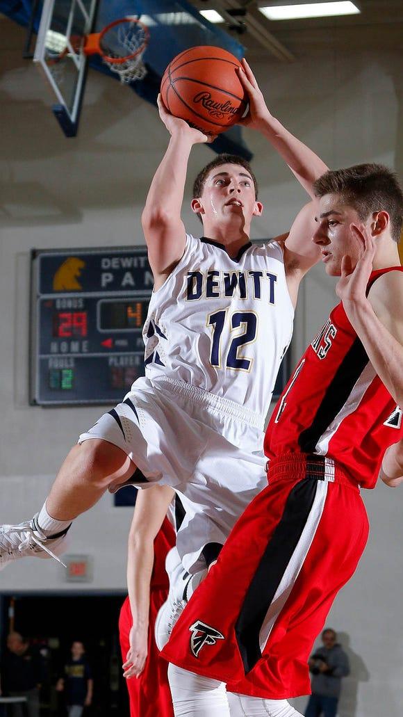 DeWitt's Donovan Tarn, left, goes to the basket against St. Johns' Alex Hudak Friday, Dec. 18, 2015, in DeWitt, Mich.