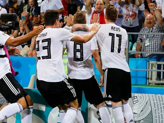 Germany players celebrate Toni Kroos' winning goal.