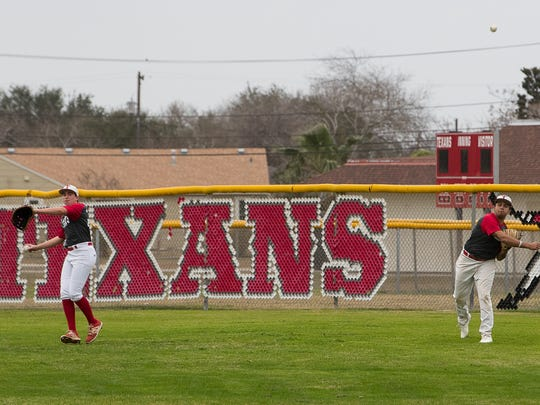 Ray High School baseball players warm up by throwing balls during the first day of practice on Friday, Jan. 26, 2018.