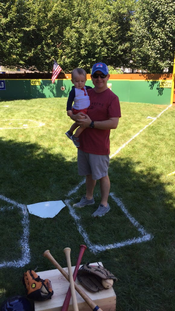 Ryan Kennedy holds his son, Luke, while standing next to home plate on the baseball field his family built in their parents' yard in Camden.