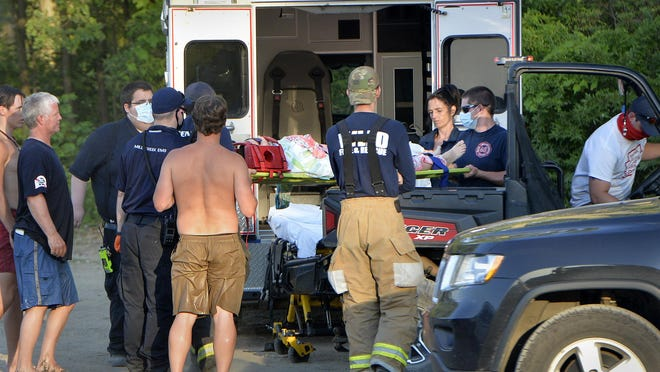 A female patient, center, is loaded into a Millcreek Paramedic Service ambulance after being injured in a boat-tubing accident in Lake Erie near Presque Isle State Park's Beach 10 on Tuesday near Erie. A Department of Conservation & Natural Resources officer said Presque Isle lifeguards brought the injured girl to shore.