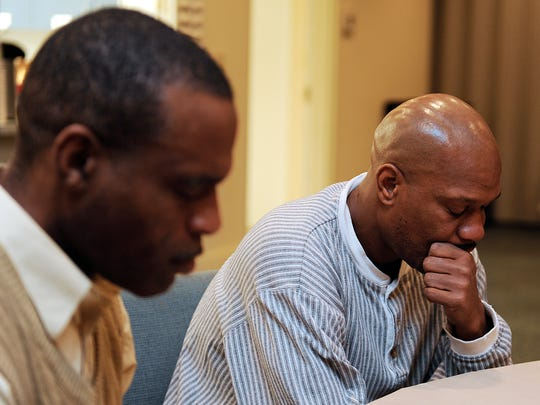 Orson Davis and Gerald Monroe pray before dinner at during there stay at Room In The Inn shelter at Franklin's Christ United Methodist Church.