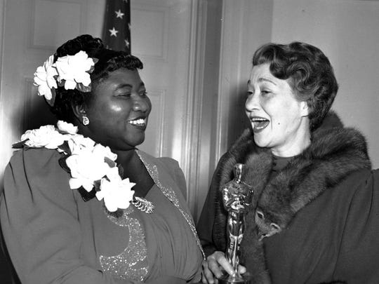 "Hattie McDaniel (left) receives the Academy Award for best supporting actress for her work in ""Gone With the Wind"" on Feb. 29, 1940, in Los Angeles."